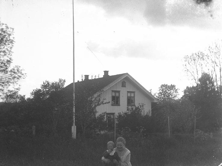 """Enl. text i blå bok: """"Villa. Dam med barn i förgrunden."""" ::"""