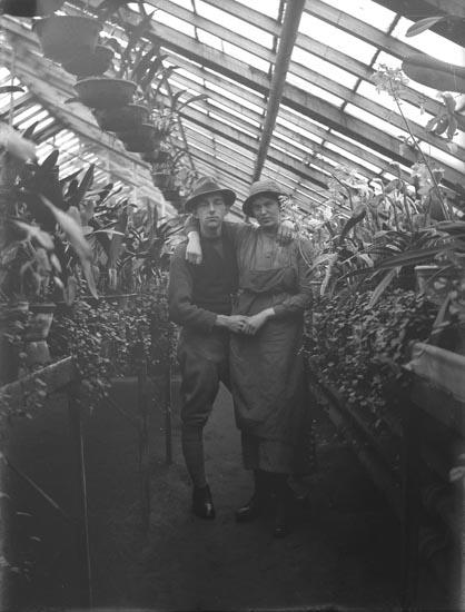 En man och en kvinna med armarna om varandra i ett växthus