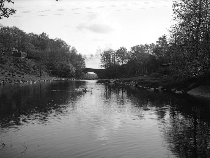 """Text som medföljde bilden: """"Nr. 46. 1930 3,5 sek. Vid Kassör Alfars trädgård och älfen, vägen till Munkedals herrgård.""""  Uppgifter från Munkedals HBF: """"Gamla stenbron, Munkedalsälven."""""""
