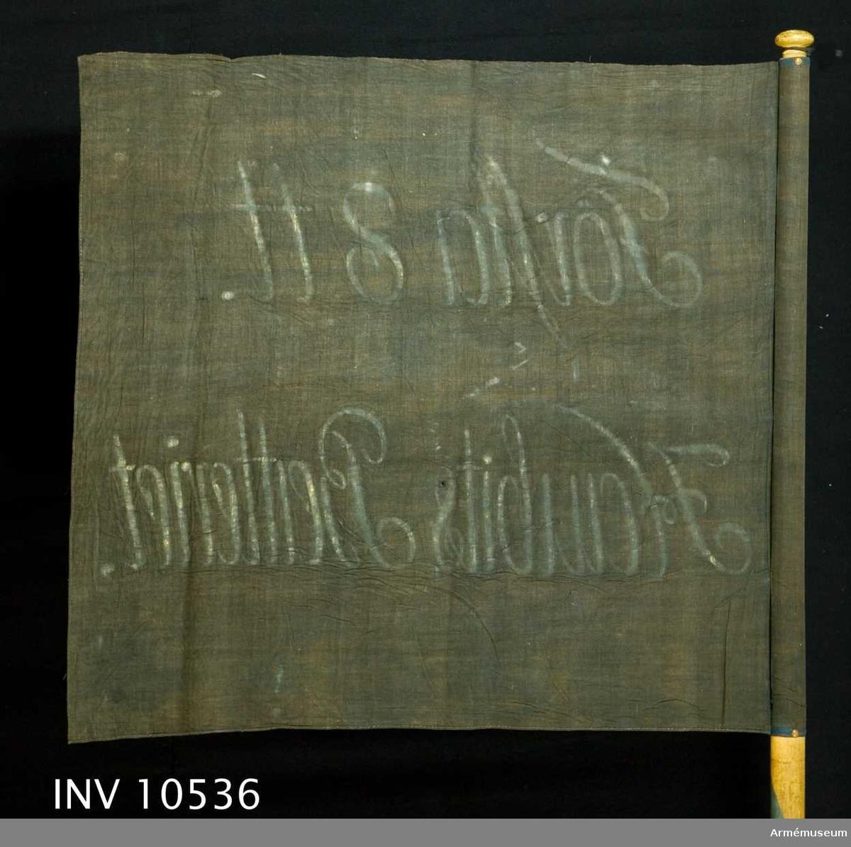 """Grupp B I.  Duk med inskrift: """"Första 8 tt Haubits Batteriet"""". Svart med gul text. """"Knopp"""" 35 mm.  Fanan är identiskt lika med AM 1932:3907 = 1975:10537."""