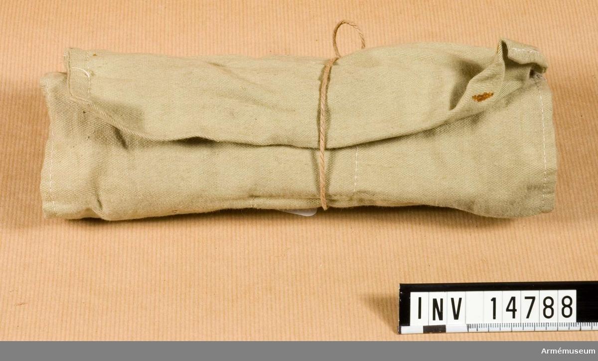 """Grupp C II Sydd av grönt bomullstyg med sju fickor för diverse hushålls- och toalettartiklar. Necessären har stämpeln  """"1917.W"""" uppåtriktad pil """"D.12"""".  Samhörande nr är AM.14780 - 14788"""