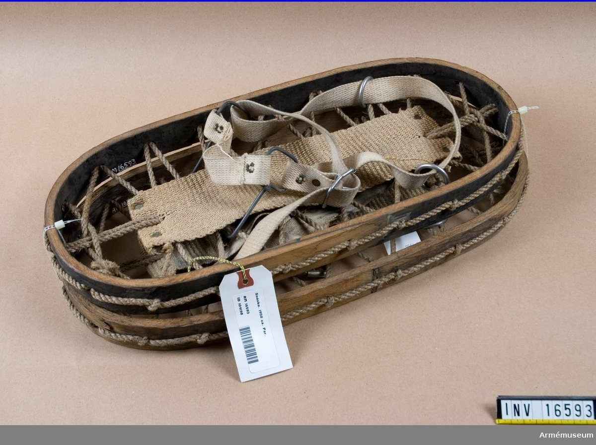 Snöskor, 1 par, ca 1950.Fotograferade.Av trä, flätat hampasnöre och förstärkt med sadelgjord. Tåremmar och sidstroppar av väv med spänne och spännringar av 3 mm järntråd.