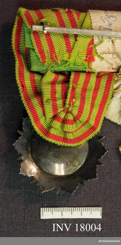 Grupp C I Ur uniform för överstelöjtnant vid indelta infanteriet, Dalregementet, 1886-1910. Tunesiska Nichan Iftikarorden, klass 3. En stjärna av tio emaljstrålar, varannan grön och varannan röd, vilande på en sol av facetterade silverstrålar. Mittskölden, bestående ytterst av en ram av facetterade silverpärlor.  Inom två strierade smala silverränder, upptager innanför ramen ett grönt emaljfält med den regerande beyens namnchiffer i silverpärlor. Ovanför solen en bandknut i silverpärlor. Bandet, med kommendörsknapp, är senapsgult med två smala röda ränder på vardera sidan.  Samhörande nr är AM.17982-18004