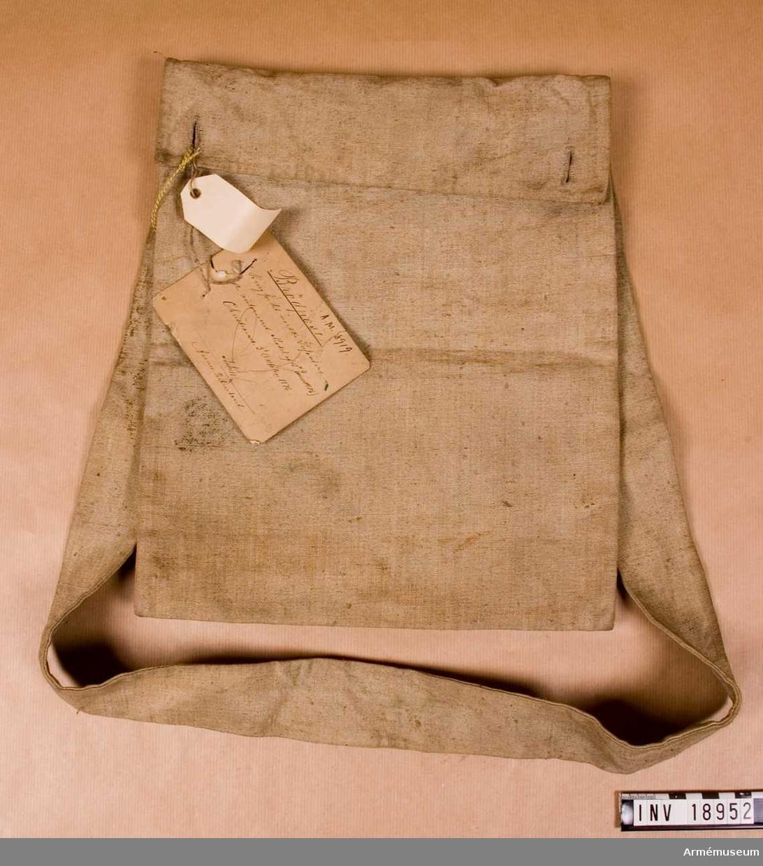 """Grupp C II. Av grov linnelärft. Lock knäpps med 2 knappar av vitmetall. Inne i påsen finns en liten påse, b:120 mm, l:110 mm, med lock och knapp. På påsens baksidan finns stämplarna """"Ni- 75"""" - 1875 och """"De"""" med krona ovanför. Påsen har gehäng av samma lärft med b:50 mm, och fastsatt på påsen baksida. Pappersetikett, på ena sidan finns sigill med text """"Intendenten för Norska Armée"""" och norska statsvapen"""", på den andra sidan står: """"Brödpåse till Brüg för det norske infanteri. Efter auktoriserad model af 15 Juni 1876"""". Christiania, 5 oktober 1876. Oläsligt namn Arméeintendent."""