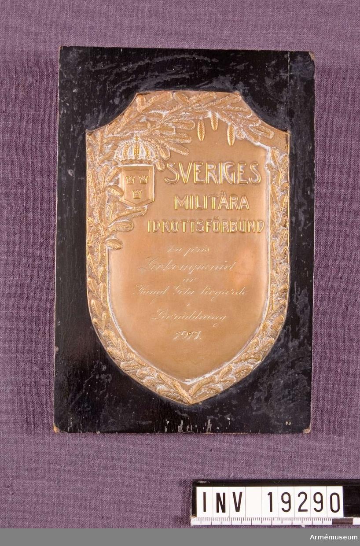 """Plakett i brons med text: """"SVERIGES MILITÄRA IDROTTSFÖRBUND 1:a pris Livkompaniet av Kungl. Göta Livgarde i Livräddning 1917."""" Plaketten fästad på svart lackad träplatta."""