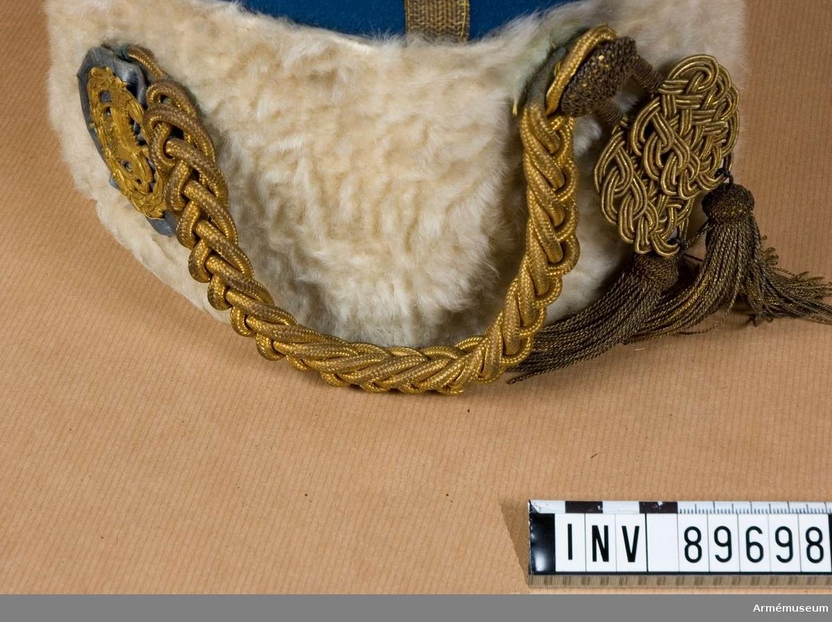 """Grupp C I. Ur uniform för officer i persiska armén. Består av mössa, vapenrock, långbyxor, kappa, aiguilette, epåletter. Av vit päls  med mösskulle av ljusblått kläde och 6 guldgaloner i kors. På mössans framsida finns rund kokard av blå kläde med persiska statsvapnet av gulmetall (krans, och i mutten lejon med svärd med kronan ovanpå). På vänstra sidan, vid mössans övre kant, finns 1 st guldknapp. Från kokarden till knappen finns hängande kordong med två tofsar, av guldsnören. LITT  Nordisk familjebok Stockholm 1928. """"Hjalmarson, Harald Ossian, militär (1868-1919) blev år 1905 kapten vid Norra skånska infanteriregementet. Efter persisk begäran 1911 om svenska officerares anställning i persisk tjänst för att organisera gendarmeriet blev H. chefinstruktör, sedan chef, för detta och överste i persiska armén. Han visade sig under fullgörandet av detta maktpåliggande uppdrag vara en framstående organisatör och blev 1913 general  i persiska armén... """"Enl kapten W Granberg."""