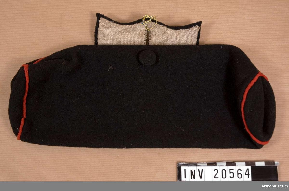 Grupp C II Av svart kläde, runt, med röd passpoal på sömmarna. Lock av samma kläde, fyrkantigt med knapphål. Knapp av svart kläde för att stänga fodralet. Foder av grov linnelärft.
