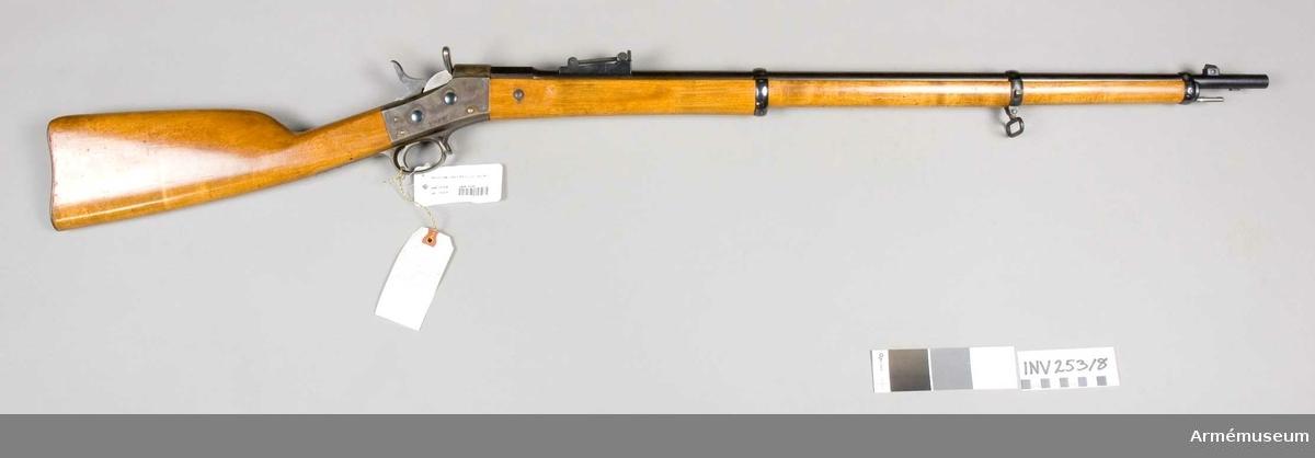 """1867 års gevär fm/1889. Första försöksmodellen. Grupp E II.  Räffelstigning 1 varv på 28,8 cm. Laddning 4,7 g komprimerat svartkrut. Kopparmantelkulans längd 30,7 mm, vikt 15,5 g. Utgångshastighet 535 m  PIPAN är rund, men har baktill ett 4,2 cm långt åttkantigt kammarstycke. En rätt hög kornklack sitter 5,3 cm bakom mynnningen. KORN av järn och med stor fot. Det är flyttbart i sidled genom att vrida på en tvärt genom kornklacken horisontal gående, från V insatt skruv. En BAJONETTKLACK sitter på undersidan 3 cm bakom mynningen.  RAMTRAPPSIKTET är placerat 6,7 cm framför lådans framkant. De tre """"trappstegen"""" är avsedda för 300, 400 och 500 m. Ramen kan fällas bakåt mot pipan och har då baktill en en siktskåra för 100 m. Ramen har på bak- eller översidan gradering för avstånd mellan 600 och 1 500 m. Till H förlängs löparen på andra sidan om siktramen och har där en siktskåra. Denna inrättning hette """"sidsikte"""" och skulle i förening med det på mellanbandets H sida befintliga sidkornet användas för avstånd mellan 1 600 och 2 000m. Graderingen för dessa håll finns på ramens undre eller främre sida. Löparen fasthålls i de olika lägena på ramen genom en fjäderspärr, som utlöses genom att trycka på en i löparens H ände befintlig knapp. På kammarstyckets översida står krönt C och på V sidan numret 87.   MEKANISMEN är av Remmingtons system och liknar m/1867-74. Lådan och varbygeln är gråhärdade, hanen och slutstycket  blanka. Mekanismen har försetts med nya, kraftigare bultar, ny, till V placerad halvmånformig utdragare samt med nytt, med centralantändning, långt, ganska smalt handtag och """"tändstiftsregulator"""" försett slutstycke. Regulatorn är en sorts hävstång, som är rörlig kring en skruv.  Den sticker upptill ut genom en urtagning i slutstyckets översida. Då mekanimen öppnas får regulatorns övre del en stöt av hanbröstet, varvid regulatorns nedre ände, vilken går i ett spår på tändstiftet, går bakåt och drager tändstiftet tillbaka tills tändstiftets spets ligger bakom sluts"""