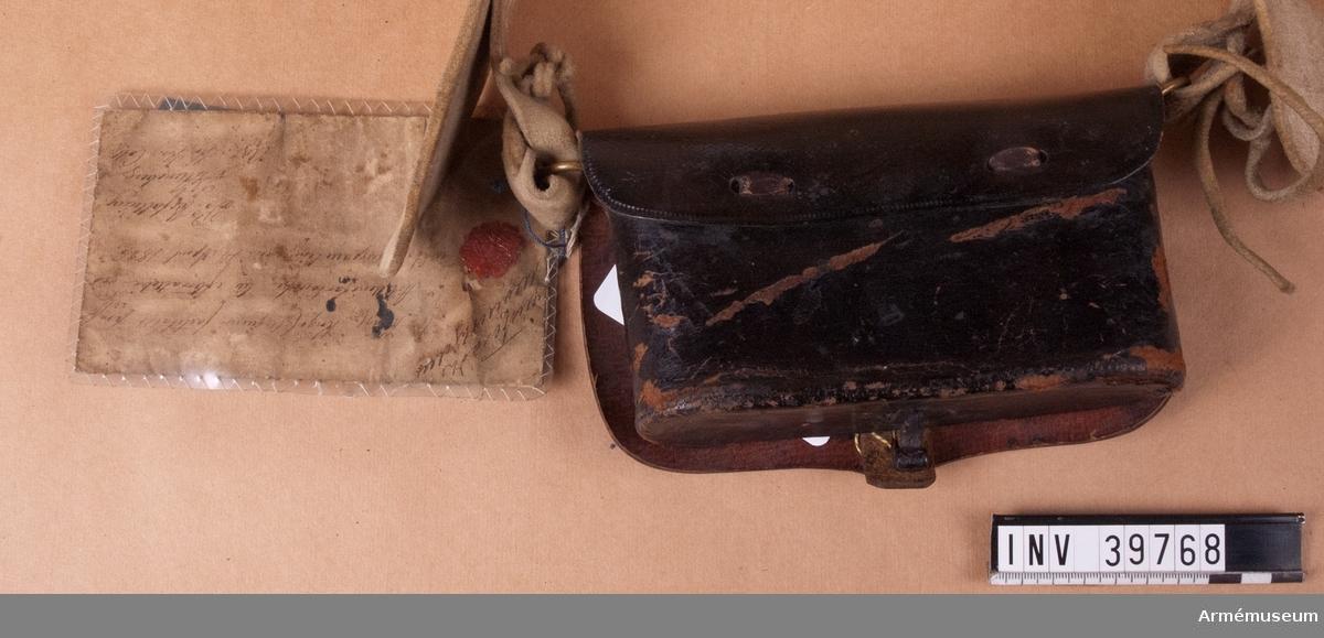 """Grupp C I. Ur uniform för manskap för Göta artilleriregemente; 1827-45. Består jacka, byxor 2 par, skärp, kask, halsduk, stövlar, sporrar, kartusch, kartuschrem, sabelkoppel, sabelhandrem. Vidhängande modellapp: """"Justeras (?)hjelm. Af Kongl. Krigs Collegium fastsäldt prof å Artillerikartousch till efterrättelse vid (?) den (?) April 1826. På Befallning (?) Adj. K. Kr. Coll."""""""