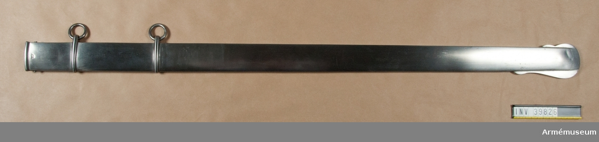 """Grupp D II.   Baljan är av järn och har flat rygg samt ett ringliknande band för var och en av de båda koppelringarna. Upptill på baljans utsida finnes en kronstämpel och på samma ställe på insidan ett ankare. På en vid baljan fäst papperslapp finnes ett rött, skadat lacksigill och påskrifter: """"Modell å balja af Jern till sablar af 1842 års Modell, med iakttagande att baljan gods skall vara 0,04 decimaltum tjockt. Stockholm den 19 februari 1844. D. W. Silfverstolpe""""."""