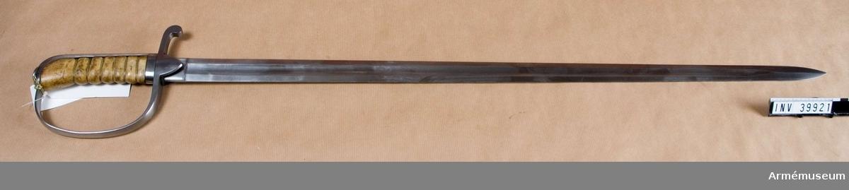 """Grupp D II.  Försöksmodell för artilleriets manskap enl. förslag av kaptenen vid Vendes artilleriregemente. Hyltén - Cavallius.  Klingans bredd upptill 3,1 cm. Klingan tillverkad i Mölntorp.Klingan är rak, tveeggad och skålslipad på mitten. Upptill på innersidan är den signerad """"C.E. SVALLING & CO. MöLNTORP"""" (är C felskrivet på katalogkort eller är märkningen otydlig? Borde vara G /1993-11 YB) och upptill på yttersidan är siffran 3 inslagen. Fästets beslag äro av järn. Kaveln är klädd med läder och har 6 refflor. Baktill har kaveln ryggbeslag, som upptill övergår i en avrundad kappa. Kappan har på översidan en rätt stor, men låg oval nitknapp. Kring kaveln och ryggbeslaget går nedtill ett 1 cm. brett ringlikande beslag. Parerstången slutar baktill i en nedböjd knapp och övergår framtill i båge i handbygeln. Från parerstångens undersida utgår ett par rätt korta, men breda, trekantiga styrskenor nedåt.J. Alm 1937."""