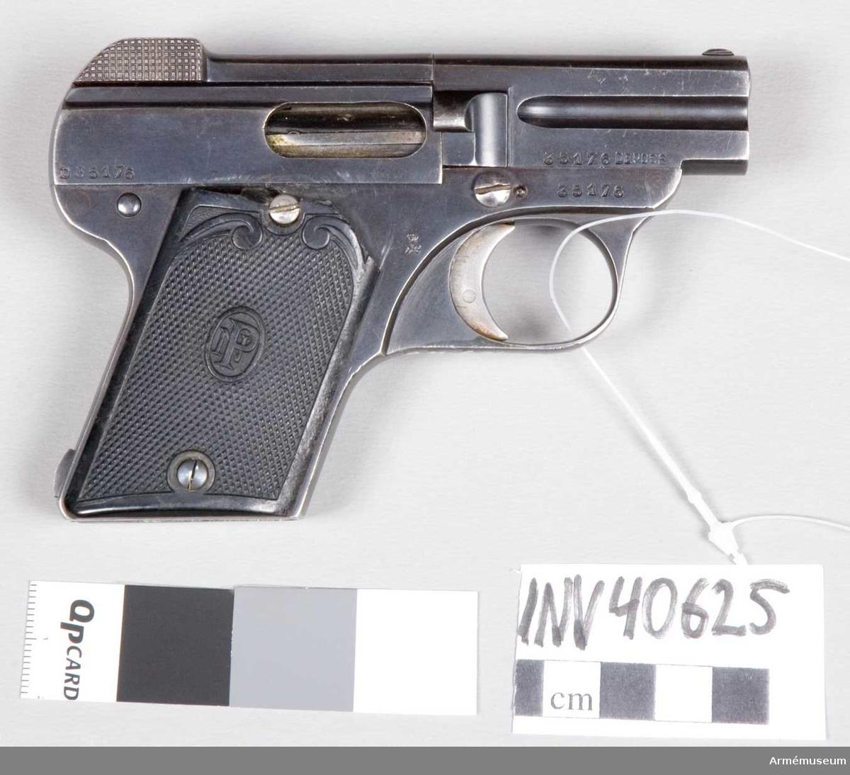"""Grupp E III. Pistolet auomatique. Tillv.nr 35176, övriga beteckningar Nr 40335, 16715/08. Pistolen är blånerad. Kolvskenorna är av svart ebonit med rutmönster. Dessa pryds med en vertikal oval medaljong med """"N.P."""" i monogram. Liegès stämpel """"ELG"""" finns på manteln."""
