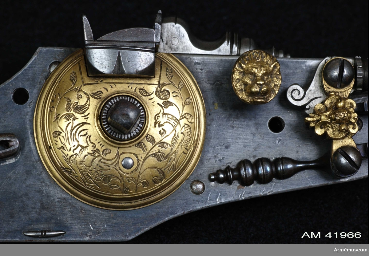 Grupp E III. Hjullåspistol tillverkad 1590 i Dresden, Tyskland.    Lika med och i par med AM.041967.  Pipan blånerad med åttkantigt kammarstycke och runt långt fält. På kammarstyckets översida en stämpel (Stöckel nr a. 54 39.515). Zacharias Herold i Dresden (1957).   Stocken är mörkbetsad al, har stor kolvkula och en småknottrig yta. Den pryds med graverade inläggningar av hjorthorn och har kring kolven, närmast kulan ett uddigt graverat silverbeslag. Baktill på kulan ett 18-uddigt silverbeslag med en lagerkrans kring Sachsens vapen (runt fält), varöver en ryttare till häst (relief).   Låset är blånerat med bland annat hjulkåpan och fängpannans spärrknapp förgyllda.  2009-12-08 EW Även säkringen, varbygeln och hanstudeln är förgyllda. Hanfjäder och säkringsfjäder är också blånerade.