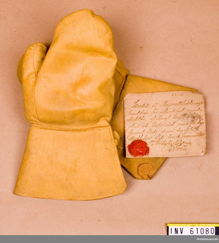 """Grupp D III.  Fäkthandske m/1868 för bajonettfäktning. Höger. .På vidsittande fastställningslapp står:    """"Modell på bajonettfäktningshandske för infanteriet, mindre  storleken, af Kongl. Majestät i nåder gillad och fastställd  genom nådiga generalorder denna dag nr: 19.""""Stockholms Slott d. 18/1 1908. På Nådigste Befallning."""