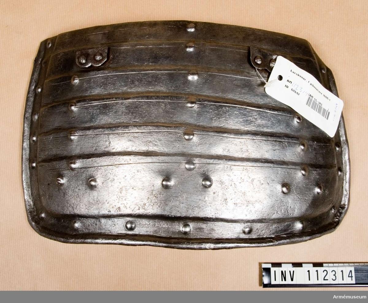 Grupp D IV. Ett par lårskenor. 1600-tal. Pikenerarutrustningen består av bröstharnesk, ryggharnesk, lårskenor, hjälm.