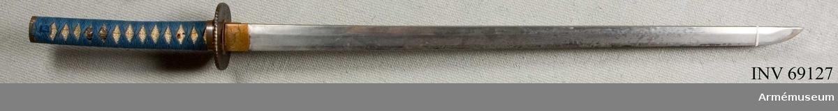 Eggad klinga av stål med fäste av en mångfald olika material (trä, järn, kopparlegering, hajskinn och silke). Har parerplåt (tsuba) av järn.