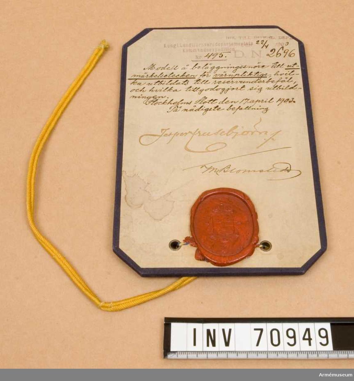 Grupp C.I. Modell å beläggningssnöre till utmärkelsetecken för värnpliktige, vilka utbildats till reservunderbefäl, och vilka tillgodogjort sig utbildningen. Stockholms Slott den 17. april 1903.