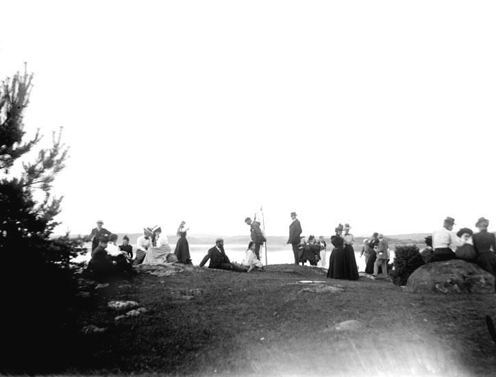 """Enligt fotografens noteringar: """"Vid Kaffet."""" Plats: Hasselön Datum: 5 Juli 1898 Tid: Kl 4.30 em. Ljus: Solsken Bländare: No 2 Objektiv: Svenska Express Exponering: Hastighet No. 3 Framkallning: Maria Lundbäck"""