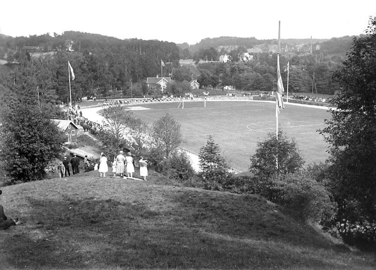 """Enligt noteringar: """"Munkedals idrottsplats. MAB:s dåvarande direktör Olof Bildt (1881-1943) lät bygga idrottsplatsen åt i första hand brukets ungdom. (Detta var ett utslag av den patriarkaliska ordning som rådde på bruket). Dir. Bildt stödde även fotbollen på annat sätt. Anl. invigdes 14/8 1927."""" (BJ)"""