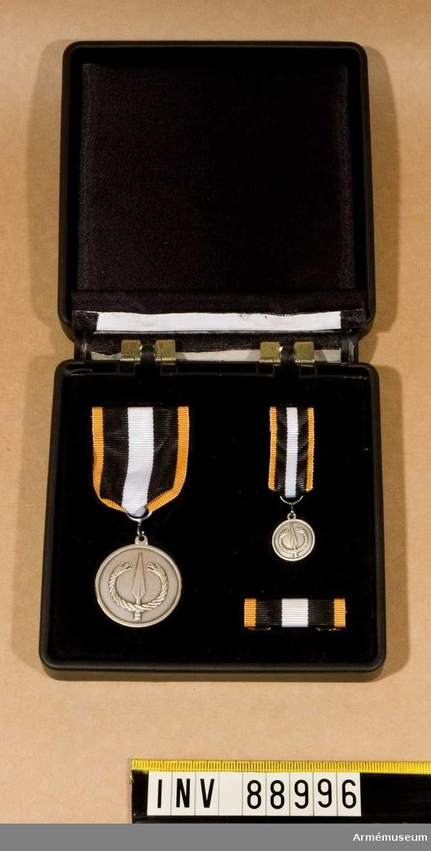 """Markstridsskolans förtjänstmedalj bestående av utmärkelsetecken i band, utmärkelsetecken i miniatyr i band och släpspänne.  Samtliga ligger i en ask. Utmärkelsetecken i band märkt på framsidan med Markstridsskolans vapen. Märkt på baksidan med texten: """"FÖRMÅGA GRUNDAD PÅ KUNSKAP OCH VILJA"""". Instansat: """"NR: 137"""" och SPORR 925 F11"""" Utmärkelsetecken i miniatyr i band märkt på framsidan med Markstridsskolans vapen. Instansat på baksidan: """"SPORR 925 F11"""". Samtliga har band i gult, svart och vitt."""