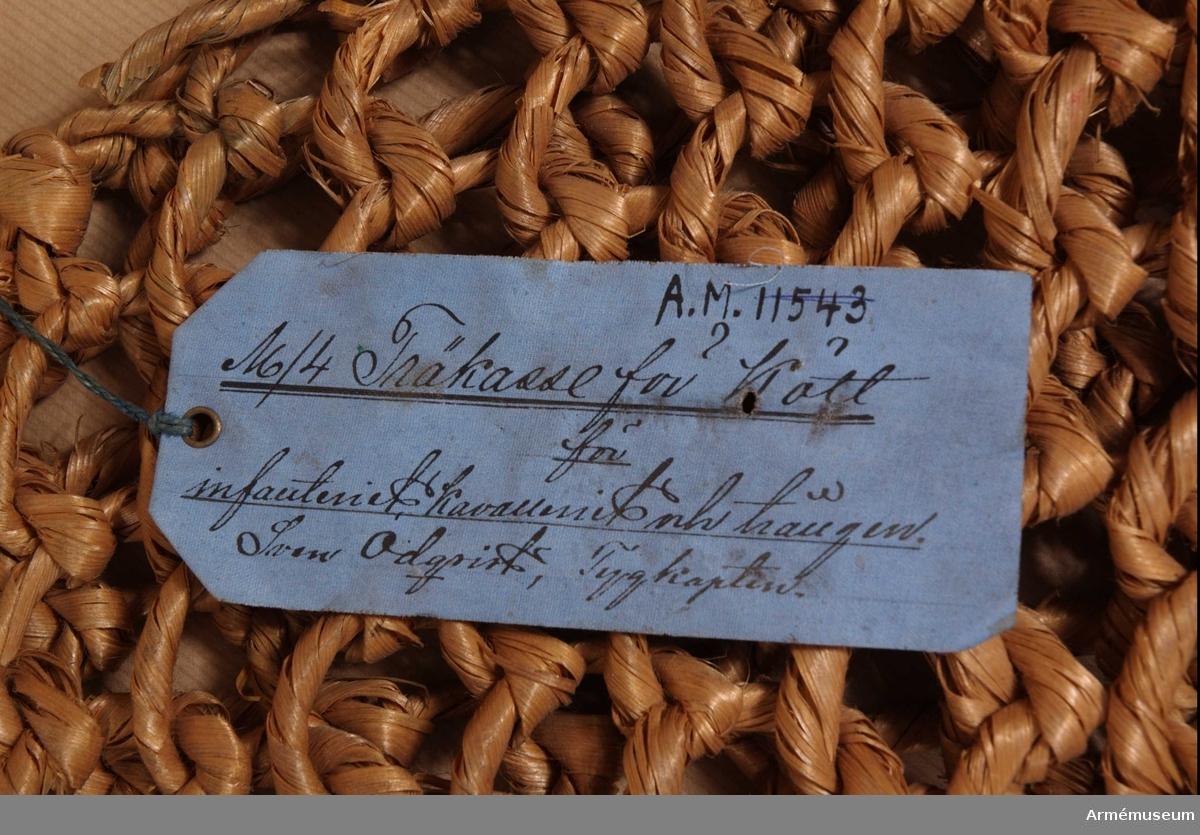 """Kasse tillverkad av träbast bunden i runda maskor. Vidhängande blå pappersetikett med text: """"No 4 Träkasse för kött, för infanteriet, kavalleriet och trängen. Sven Odquist, tygkapten""""  KTS 2012-02-01"""