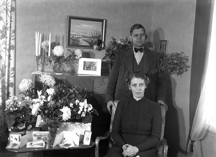 """Text till bilden:""""Man och kvinna firar högtidsdag. Interiör""""."""