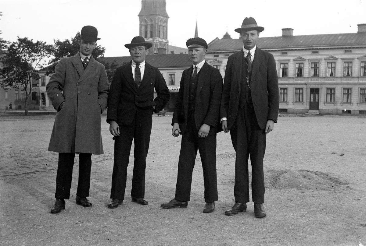 Fyra män, Gustav Andersson längst till höger, står på Västra torget i Jönköping med hus och Sofiakyrkans torn i bakgrunden.