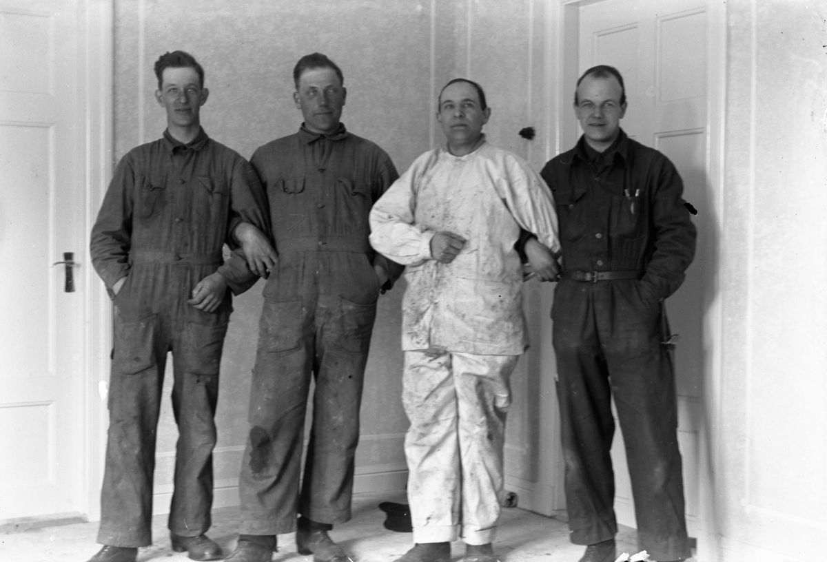 Fyra män klädda i overaller står i ett rum mellan två dörrar.