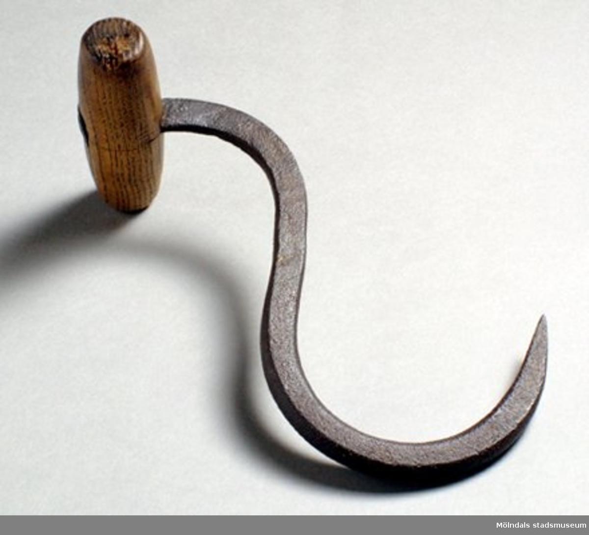 S-formad järnkrok  - rostig. Väl använt och slitet trähandtag, något sprucket. Från 1900-tal. Har eventuellt använts för att lyfta pappersbalar eller dylikt med.