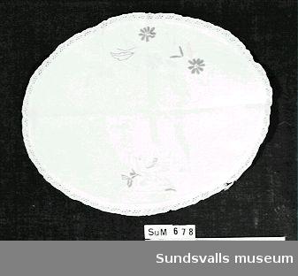 Brickduk med broderat mönster av blommor, blad, samt en fågel i rött, gult och vitt. Broderad i plattsöm och kedjestygn. Påsydd spets.