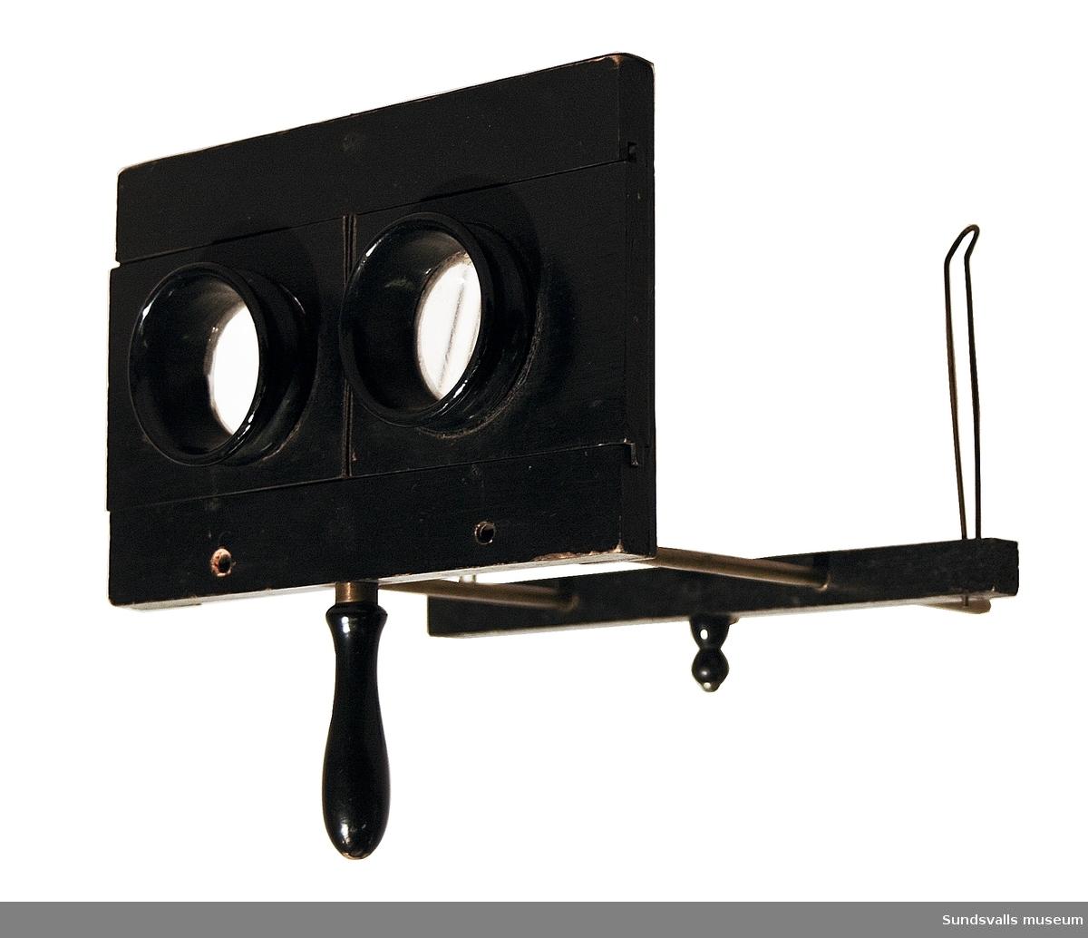 Stereoskop, svartmålat med svarvat handtag. Linserna kan ställas in genom att skjutas åt sidorna. Veckat papper mellan linshållare. Bildhållare flyttas på två parallella mässingsrör.