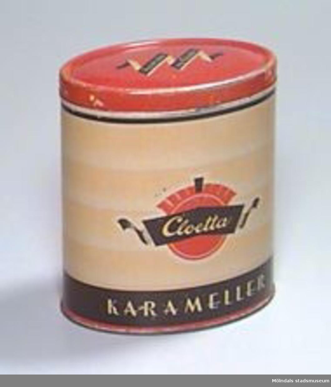 """Oval hög burk med lock. Målat i svart, rött och gult: """"Tag det rätta, tag Cloetta"""" på locket, """"Cloetta karameller"""" på sidorna."""