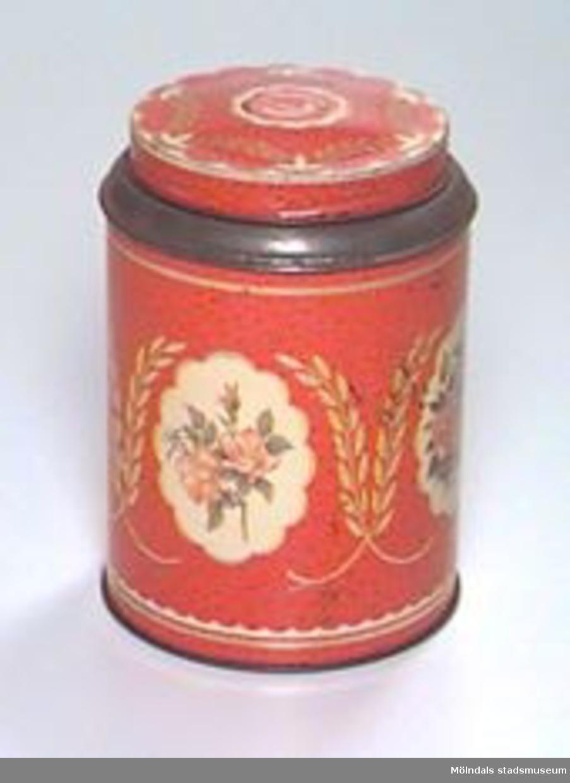 """Rund hög burk med lock. Rödmålad med guldfärgad dekor och blommotiv i olika färger. På locket: """"Kärnkaffe kaffet med arom"""".Rispig, rostig.Tidigare sakord: burk med lock"""