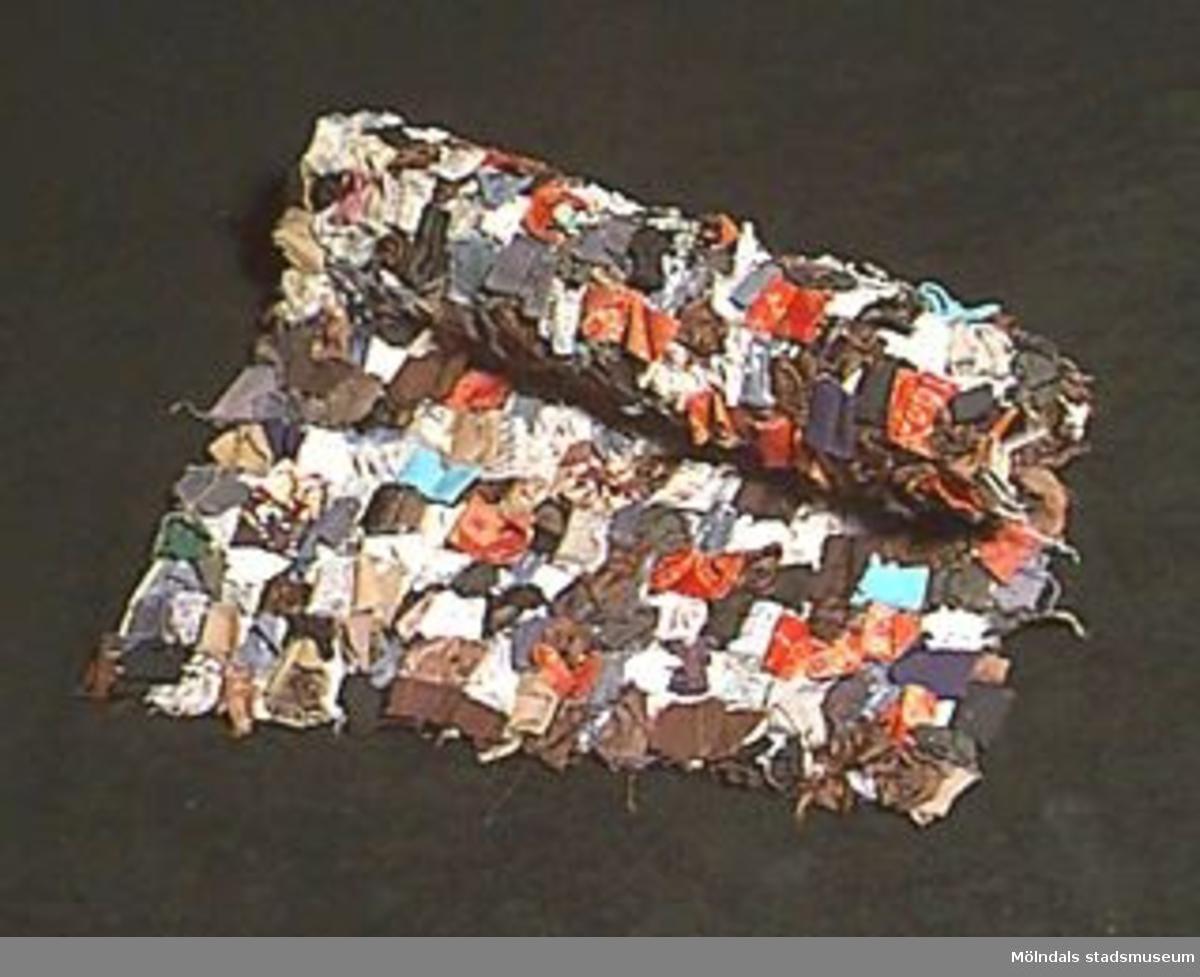Polykrom matta med trasor syddda på dubbel linnebotten. Trasorna  i olika storlekar, tyger, (bomull, konstfibrer, blandat), vävda och tryckta mönster från 1930-1960-tal.Smutsig.