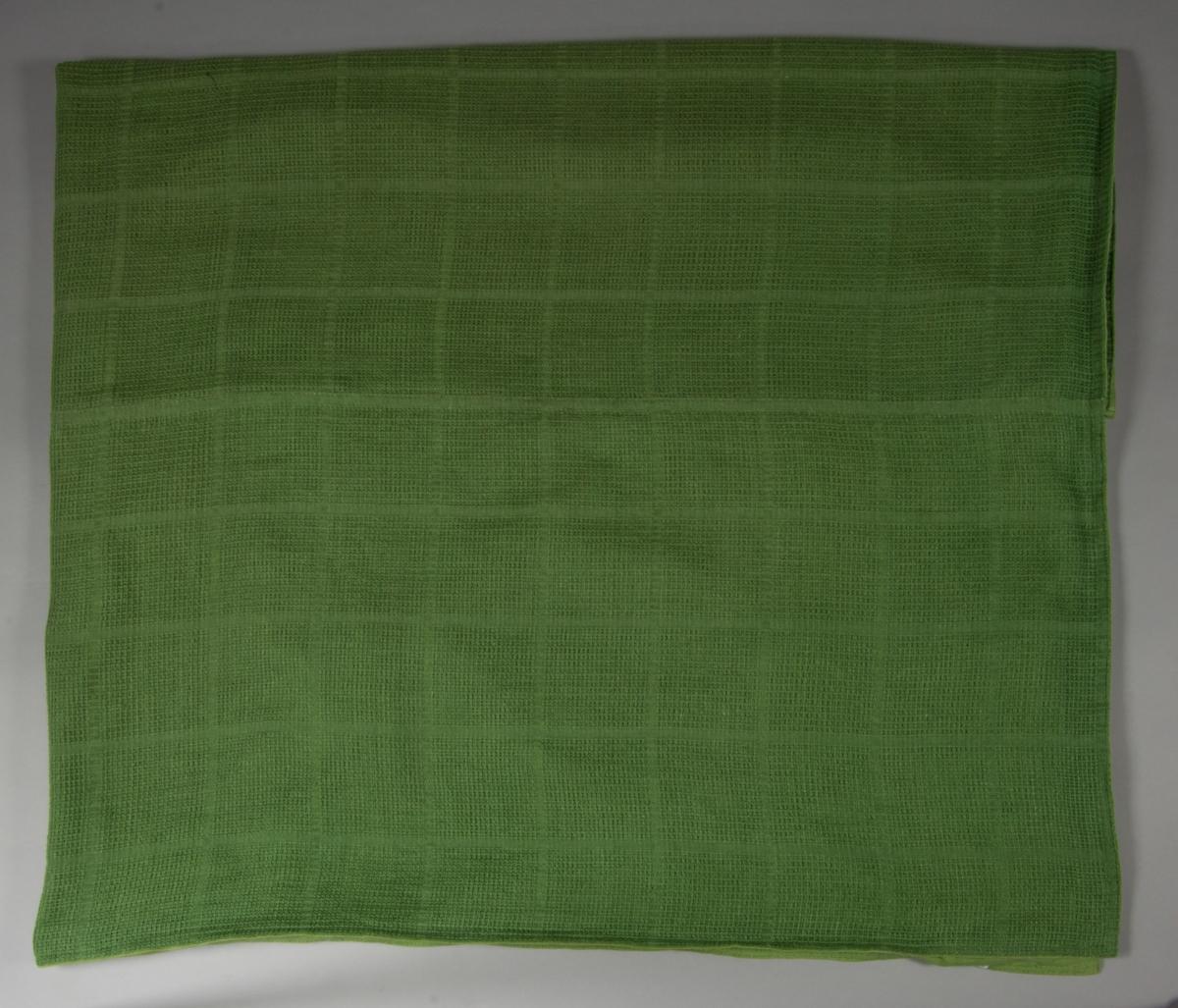 Överkast till säng. Tillverkat av handvävt linnetyg., mörkgrönt, vävt i stramaljbindning, myggtjäll med stora rutor. Två våder hopsydda på mitten, hörnen formade för att passa omstopp och nedhängande del fram. Sidorna, nedre kanten fram och den tänkta viklinjen för nerhänget kantade med gröna linneband. Överkastet är helfodrat med grönt linnetyg i tuskaft.