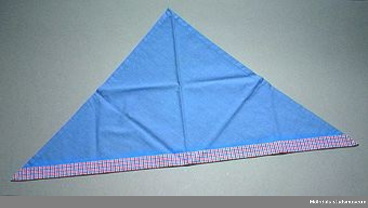 En skolkökssnibb i blått och rosablåvit-rutigt tyg. Undervisningsmaterial för årskurs 6. Samhör med 02663-02669. Övriga uppgifter se 02643:1.