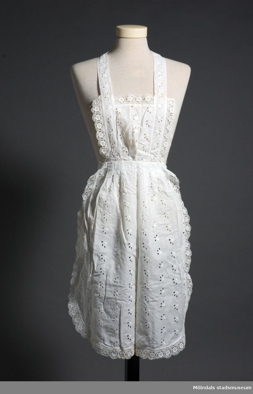 Helvitt spetskantat förkläde. Det tunna bomullstyget är hålbroderat vilket bildar ett mönster. Rynkat vid midjan samt band att knyta runt hals och midja. Något gulnat.
