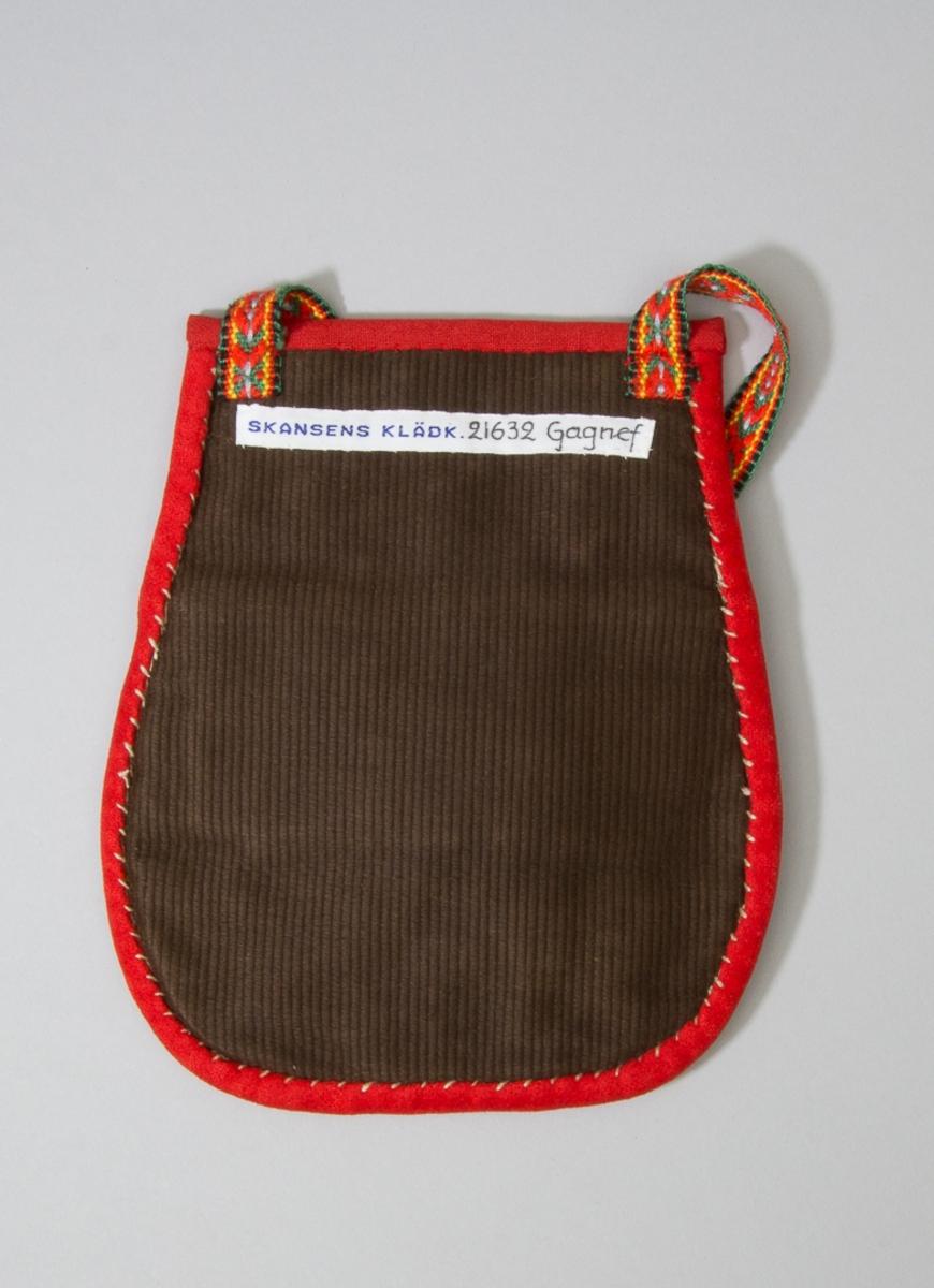 Kjolsäck till dräkt för kvinna från Gagnefs socken, Dalarna. Modell med avskuret framstycke. Tillverkad av mörkblått ylletyg, vadmal, med applikationer av kläde i rött, grönt och gult, fastsydda med läggsöm sydd med ullgarn i rött och blått. Centralt placerat hjärtmotiv omgivet av hjulformer. Ytan mellan applikationerna fylld med broderi utfört med ullgarn i många färger, sticksöm. På överstycket också broderat med samma ullgarn, sticksöm och flätsöm. Framstycket fodrat med troligen fabriksvävt vitt linnetyg, tuskaft. Kantat runtom med remsor av rött kläde. Bakstycke av fabriksvävt brunt bomullstyg, randstruktur. Midjeband fabriksvävt av ullgarn i rött, grönt, gult, ljusblått och svart.