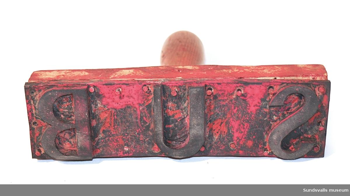 Stämpel i gummi med handtag i trä. Stämpeln visar bokstäverna SUB. Röda färgrester finns kvar på stämpeln.