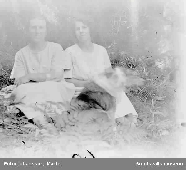 Två kvinnor och en hund i skogsmiljö.