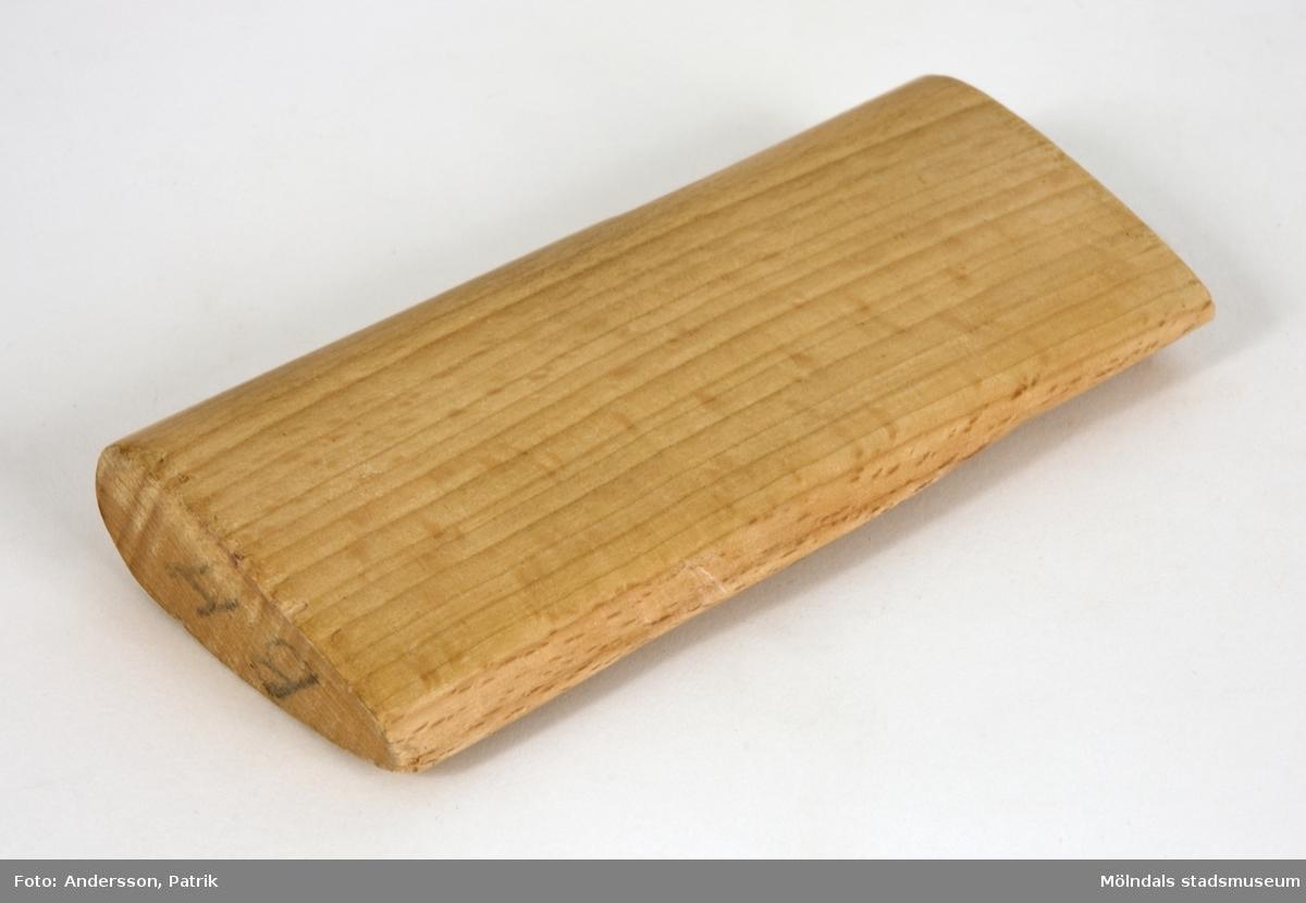 """Träverktyg, troligen tyngd, som har använts vid papperstillverkningen på Papyrus. Verktyget är droppformat i genomskärning, och är märkt med initialerna """"BH""""."""