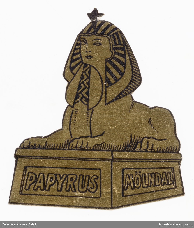 """2 st guldfärgade sfinxmärken som användes som Papyrus loggan.Text på sfinxmärket/loggan (tryckt i svart): """"PAPYRUS MÖLNDAL""""Storlek på sfinxmärket:Längd: 70 mmBredd: 57 mm"""