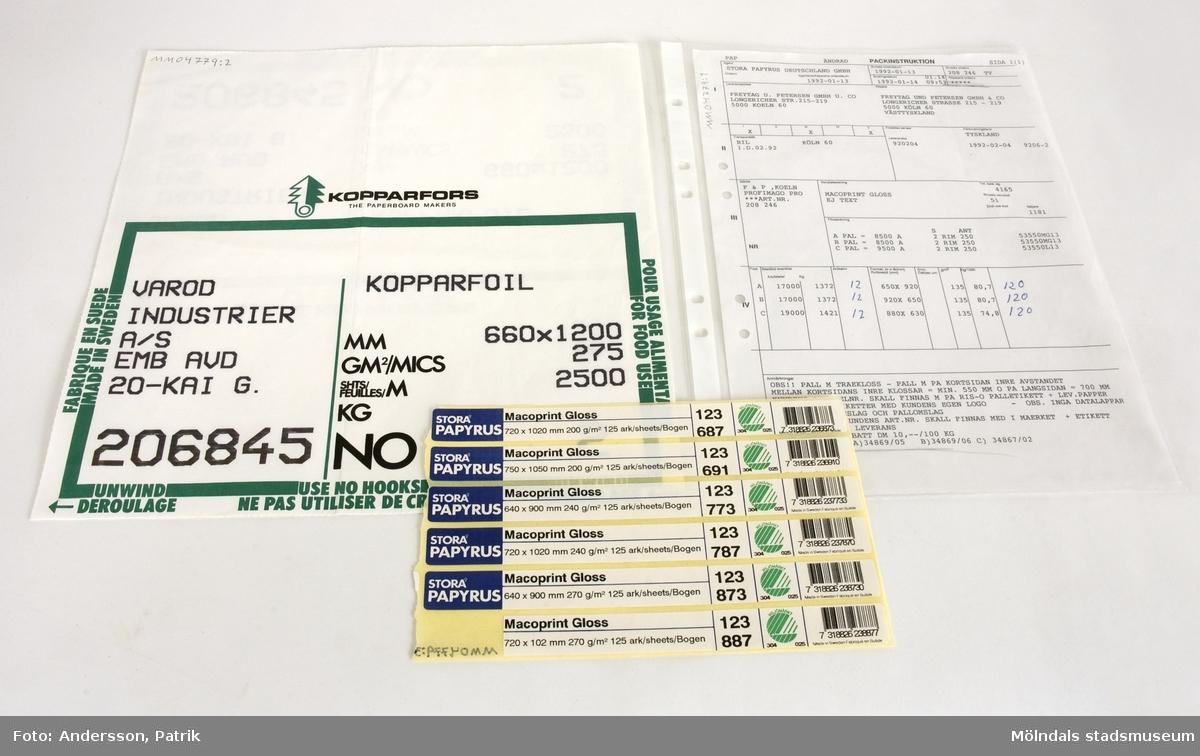 """1 st palletikett som finns i 3 st kopior. Dessa sitter också ihop så att det är ett stort ark.Etiketten är vit med en grön bård runt. I bården står uppmaningarna: """"FABRIQUE EN SUEDE MADE IN SWEDEN"""", """"POUR USAGE ALIMENTAIRE FOR FOOD USE"""", """"UNWIND DEROULAGE"""", """"USE NO HOOKS NE PAS UTILISER DE CROCHET"""". Längst upp på etiketten finns loggan: """"KOPPARFORS THE PAPERBOARD MAKERS""""Uppgifter som finns på etiketten:""""VAROD    KOPPARFOILINDUSTRIERA/S EMB AVD20-KAI  G.MM 660x1200GM2/MICS 275SHITS/FEUILLES/M 2500206845    NO 2""""Storlek på palletiketten:Längd:  304 mmBredd:  296mmAnvändningstid: 13/1-1992 - 4/2-1992"""