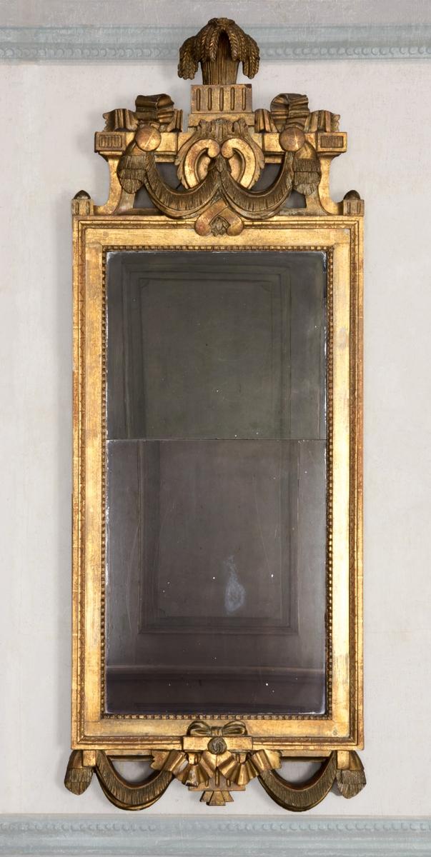 Spegel med snidad och förgylld träram och överstycke. Rikt dekorerad med girlanger, lagerblad och urna. Gustaviansk stil.