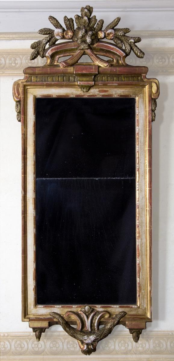 Spegel, stockholmsarbete, av trä. Med skuren och skulpterad dekor. Genombrutet krön i form av bukett av blommor, frukter och ax sammanhållet med band. Krönets dekor viker runt ramens kant i form av skurna voluter och tofsar. Ramens inre profilering med bandstavsliknande dekor. Ramens underkant i form av en djupt hängande rocaille och mussla bakom bladgirlang, kantad av två nedåthängande knoppar. Förgylld med polerat guld och slagmetall. Med delat kvicksilverfolierat glas.