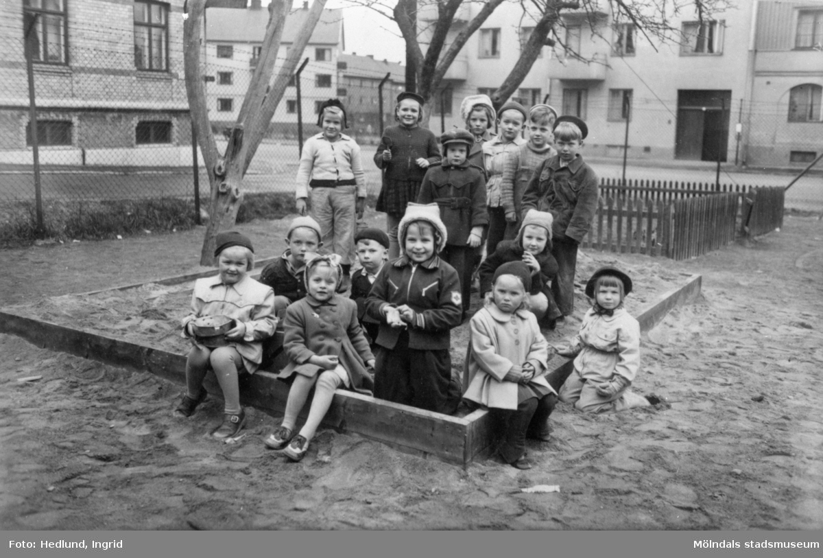 Några barn som står i en sandlåda uppställda för fotografering. Okänd plats 1945-.