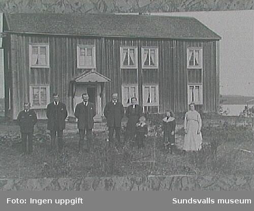 Familjebild från ca 1915 framför nya bostadshusetuppfört 1824. Fr. v. : Lorentz Söderblom, f 1900-12-03 Helmer Söderlund f 1896-05-17, EmilSöderblom, f 1888-04-16, hemmansägare O P Söderblom, f 1858-12-09 ( far till de tre förgående), hustrun Johanna Söderblom, f 1864-09-24, barnbarnet Harry Söderblom, f 1911-03-11 (utvandrade till USA 1928), dottern Siri Söderblom, f 1905-01-17 samt pigan Anna Elida Nordlund från Ortsjön. Observera att det ännu finns ett brotak över entrén samt att de ursprungliga ytterdörrarna finns kvar.