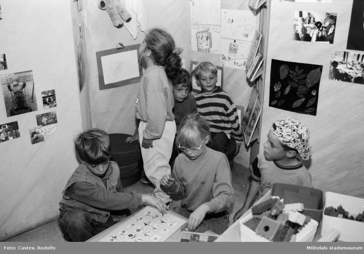 Tre barn som pysslar med något på golvet. Några barn tittar på saker som är uppsatta på en vägg. Utställningsvernissage av och om Katrinebergs daghem på Mölndals museum 1993-09-10.