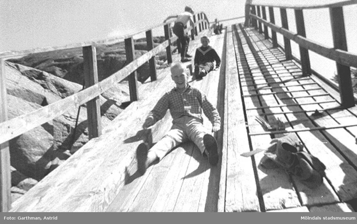 Ungdomar (okända för givaren) åker rutschkana på en transportbana i Guldheden. De är på skolresa från Kvarnbyskolan, 1958-59.