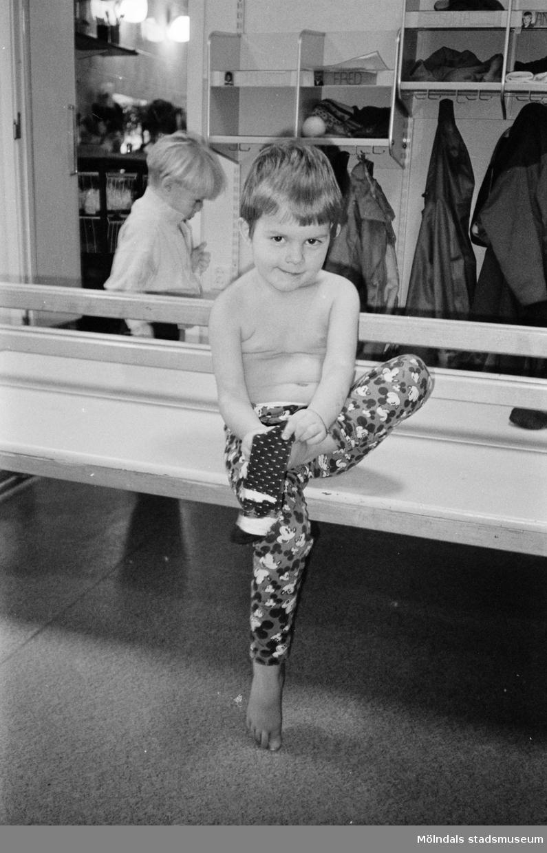 Alexandra sitter på en träbänk inomhus och sätter på sig sockor. Hon har naken överkropp och Musse Pigg-tights. Lunkentussen, Katrinebergs daghem 1992.